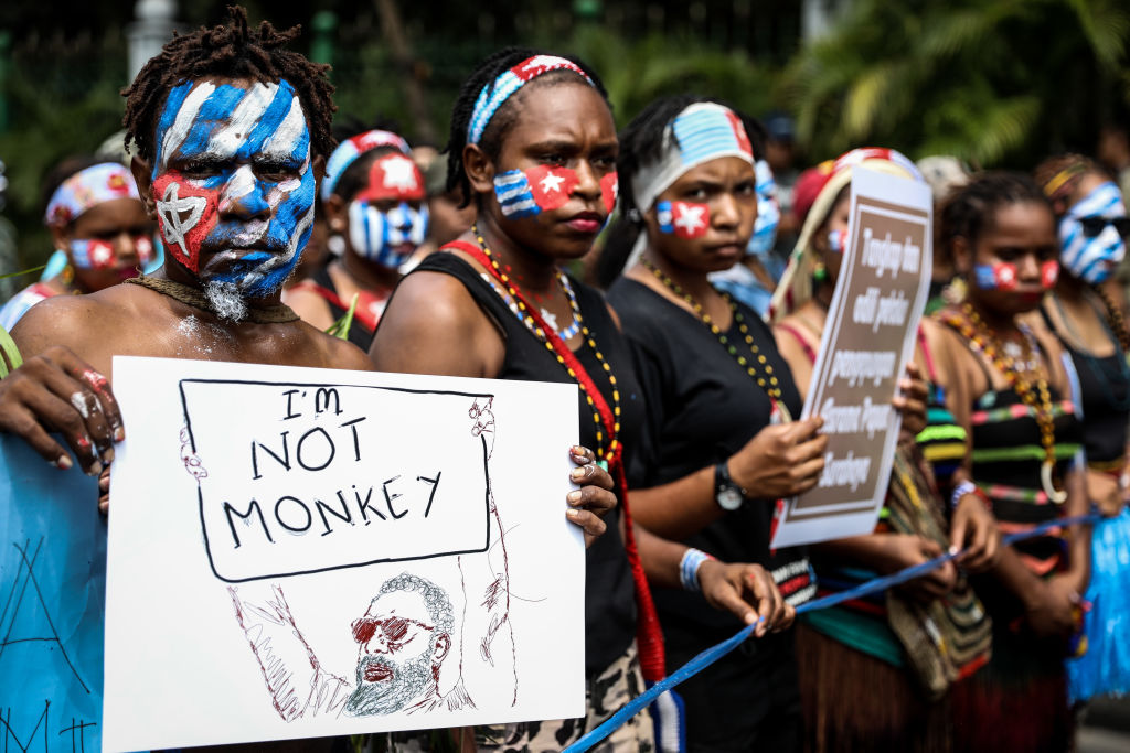 Protesters with West Papua flag painted on their face, holding sign that says I'm not a monkey