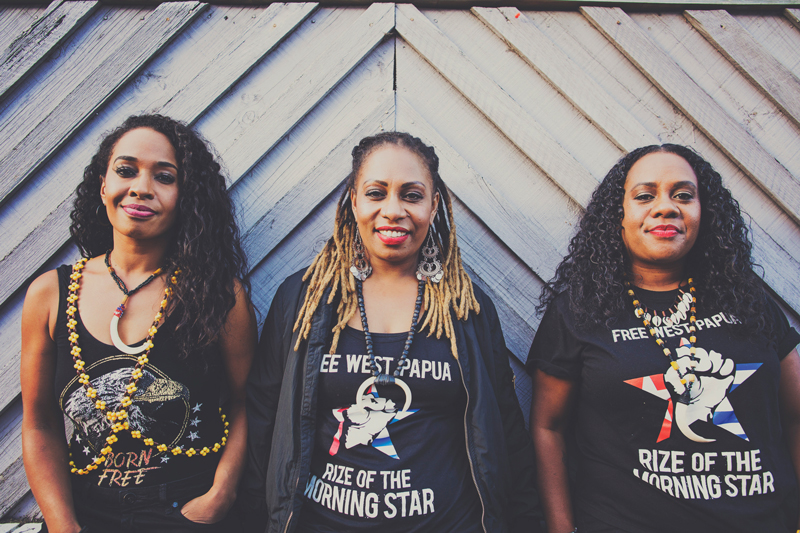 The Black Sistaz standing against wooden wall, smiling wearing Free West Papua t-shirts